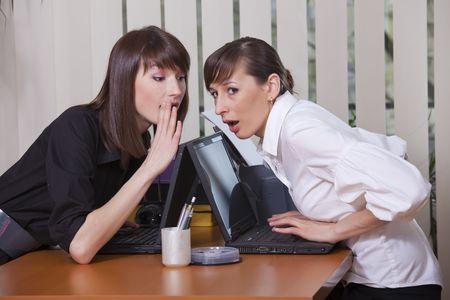 gossip: twee jonge vrouwen gossip in een kantoor
