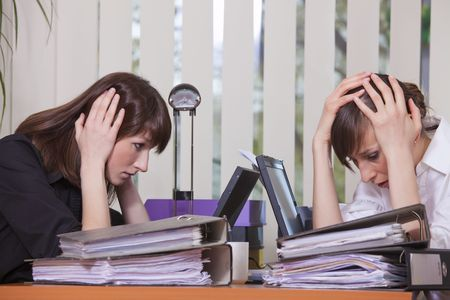 two frustrated businesswomen by work in the office photo