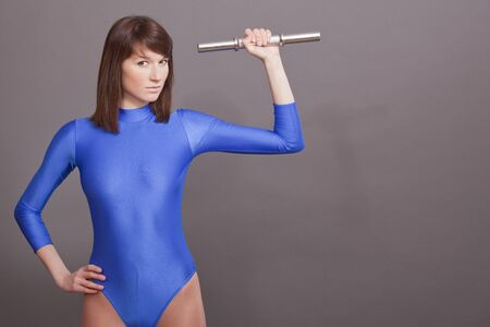 lycra: young woman in blue leotard holding silver dumbbell Stock Photo