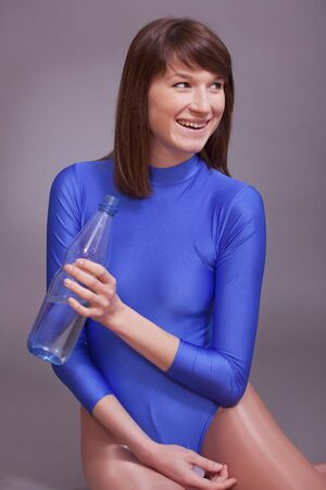 lycra: young woman in blue leotard holding bottle of water and laughing