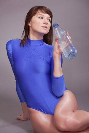 leotard: young fitness woman in blue leotard drinking water after sport exercises Stock Photo