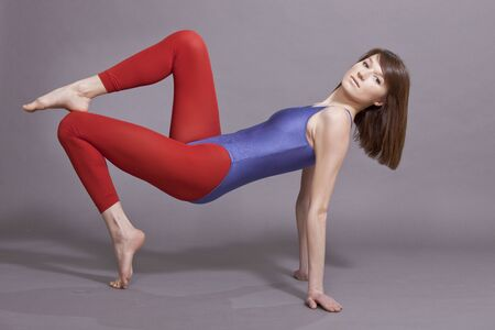 lycra: young woman in leotard working out on the ground