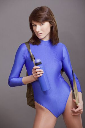 lycra: young woman in leotard standing with her sports bag and bottle of water, ready for the training