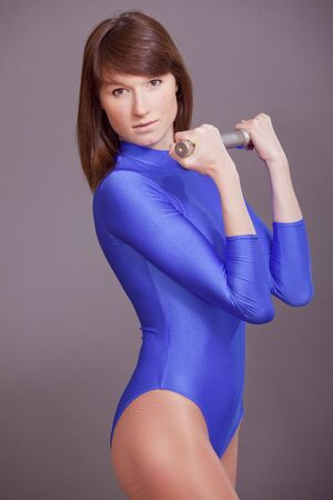 lycra: pretty young woman in blue leotard doing exercises with dumbbell