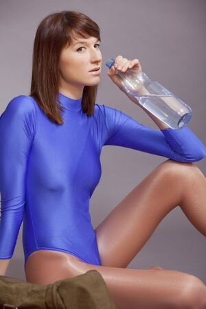 lycra: fitness woman in blue leotard drinking water after training