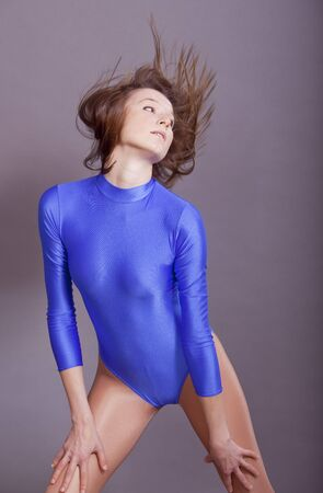 lycra: young dancing woman swinging her hair in studio