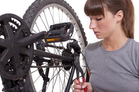 고치다: woman fixing a gear on bicycle - shot in studio