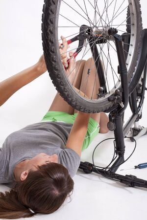 woman with plier repairs a bicycle - shot in studio Stock Photo - 7204506
