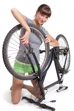 reparaturen: Frau Reparaturen Fahrrad mit Zange - shot in Studio auf wei�em Hintergrund