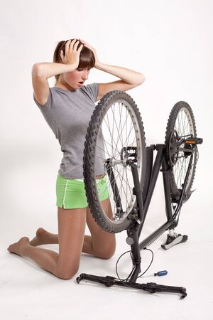 defect: woman in trouble looking at her defect bicycle