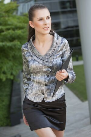 young and happy businesswoman walking with folder photo