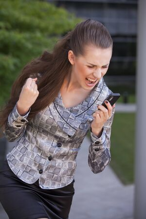 angry businesswoman screaming on cell phone outdoor photo