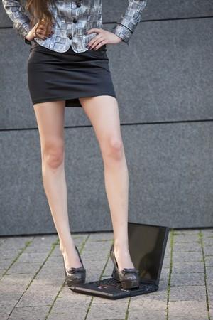 female foot in a shoe on laptop keyboard photo