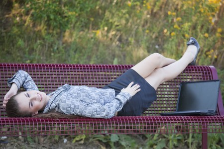 businesswoman relaxing on the bench in park photo