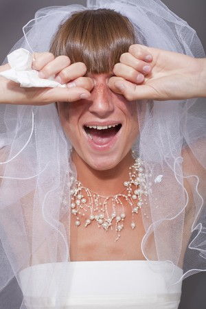 portrait of crying bride over grey background photo