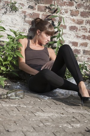 drunk young woman in black leggings lying on the ground photo