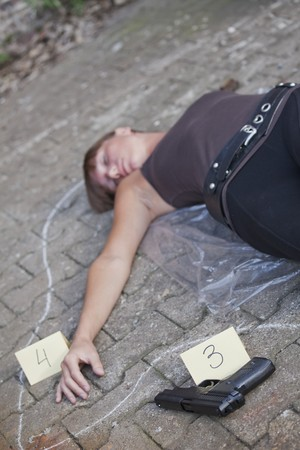 unconscious: crime scene - outline of young dead woman with gun and placard on the ground