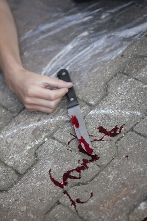 gruesome: crime scene - female hand with bloody knife on the ground