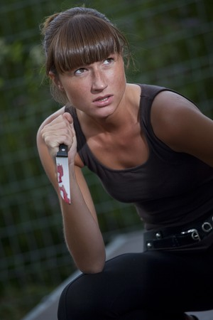 angry woman with bloody knife in her hand outdoor photo
