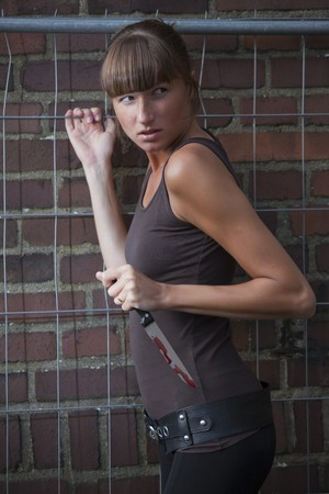 armed young woman with bloody knife in the hand photo