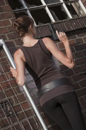 brocken: young woman with gun standing at the brick wall