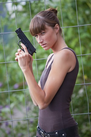 young female agent with a gun outdoors photo