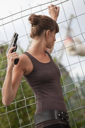 female agent with gun looking for something outdoor photo