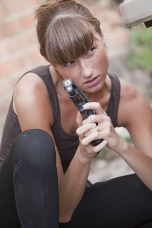 sexy female agent with a gun hiding photo