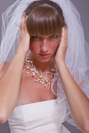 frustrated bride holding her head with both hands photo
