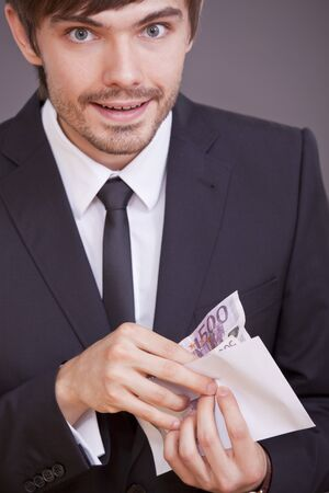 happy businessman holding money in envelope over grey background Stock Photo - 7515588