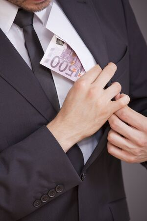 young businessman taking bribe over grey background photo