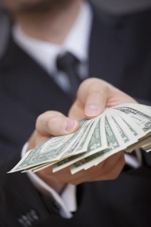giving money: businessman holding american dollars