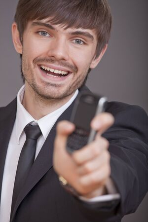 laughing businessman showing cell phone in the camera over grey background photo