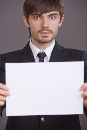 young businessman holding white blank board to write your own message photo