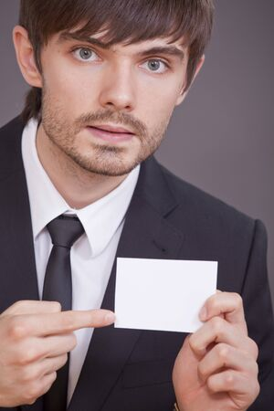 businessman pointing with his finger on blank visit card over grey background photo