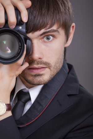 male photographer in business suit taking a picture photo