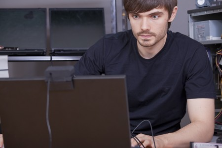 male computer technicians in black shirt working on laptop