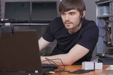 webcam: male programmer with headset working on laptop computer