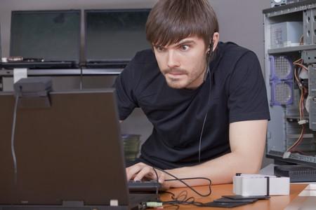 programmer computer: computer hacker in black shirt working at laptops  Stock Photo
