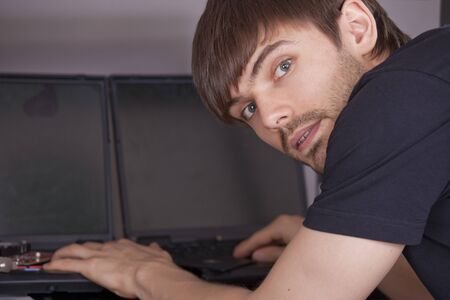 computer technician in black shirt typing on laptops photo