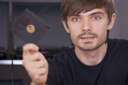 hacker holding floppy disk with data in the hand photo