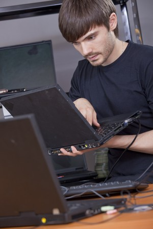 computer: male computer technician installing new software on laptop