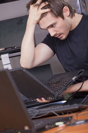 computer trouble - male technician looking in despair on laptop photo