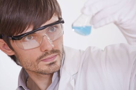 chemical researcher with colourful flask in a lab photo