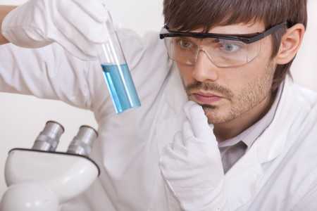 thinking male researcher with a blue liquid test tube - over a white background