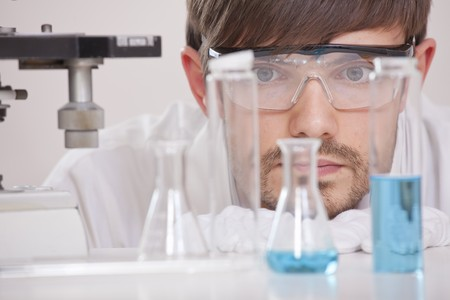 thinking male chemical researcher with manycolourful flasks in a lab photo