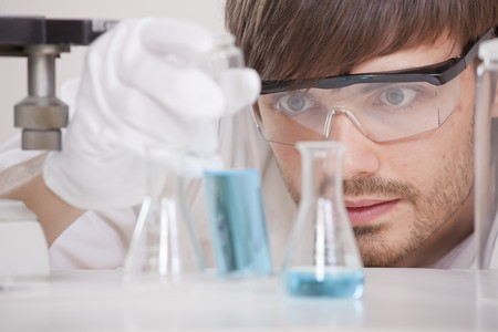 male scientist in research lab holding glass flask with blue fluid