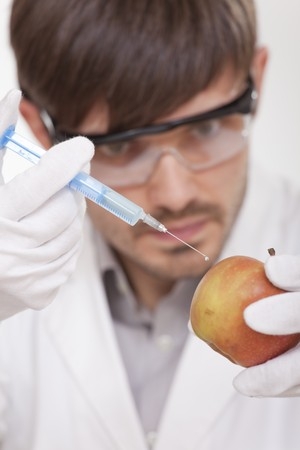male scientist with syringe injecting apple photo