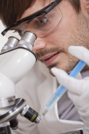 Scientific Research - man looking in microscope with syringe in his hand