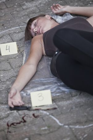 unconscious: crime scene with killed woman and bloody knife on the ground